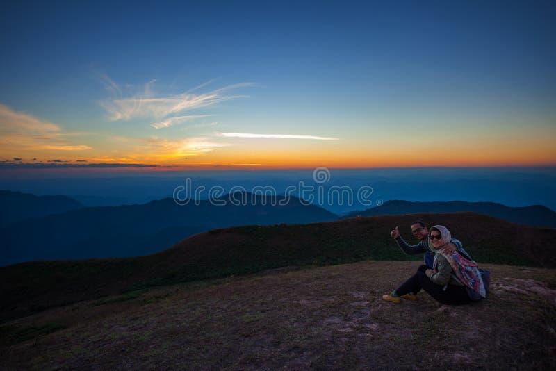 Coppie dell'uomo e della donna che si siedono sopra la scena della montagna con la b immagini stock