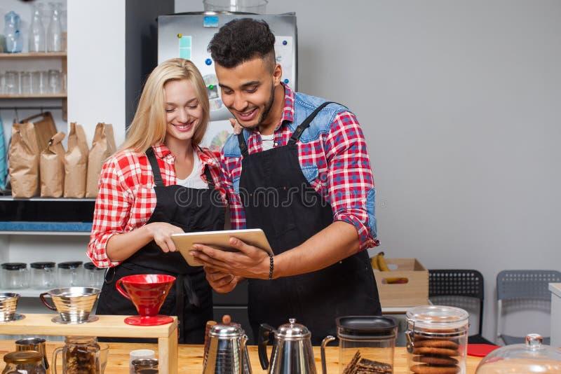 Coppie della caffetteria di barista facendo uso del sorriso felice del computer della compressa fotografia stock libera da diritti
