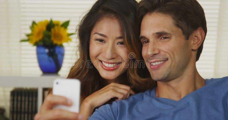 Coppie della corsa mista che prendono i selfies fotografie stock