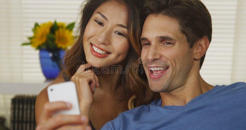 Coppie della corsa mista che prendono i selfies fotografia stock