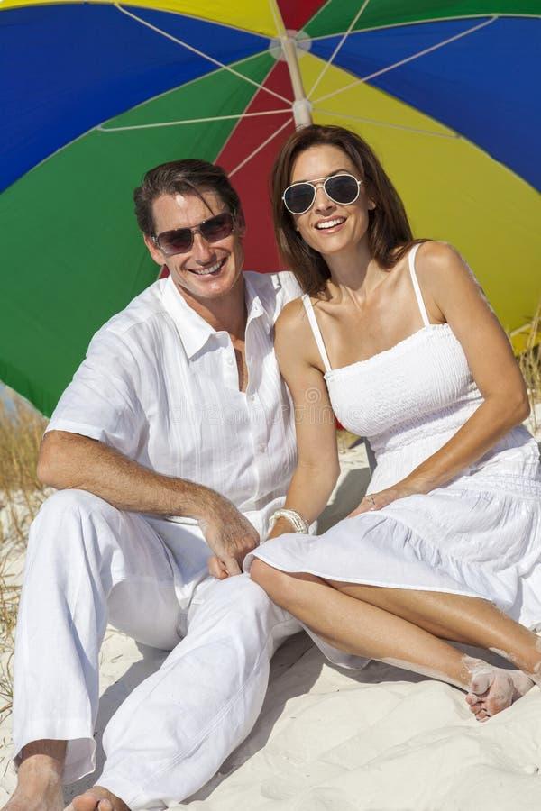 Coppie della donna & dell'uomo sotto il multi ombrello colorato sulla spiaggia fotografie stock libere da diritti