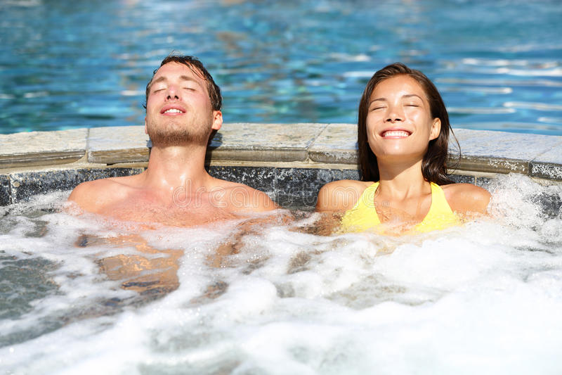 Coppie della stazione termale che si rilassano godendo della vasca calda della Jacuzzi immagini stock libere da diritti