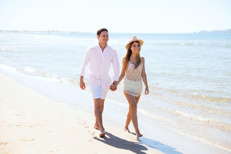 Coppie delle persone appena sposate che camminano giù la spiaggia fotografia stock libera da diritti