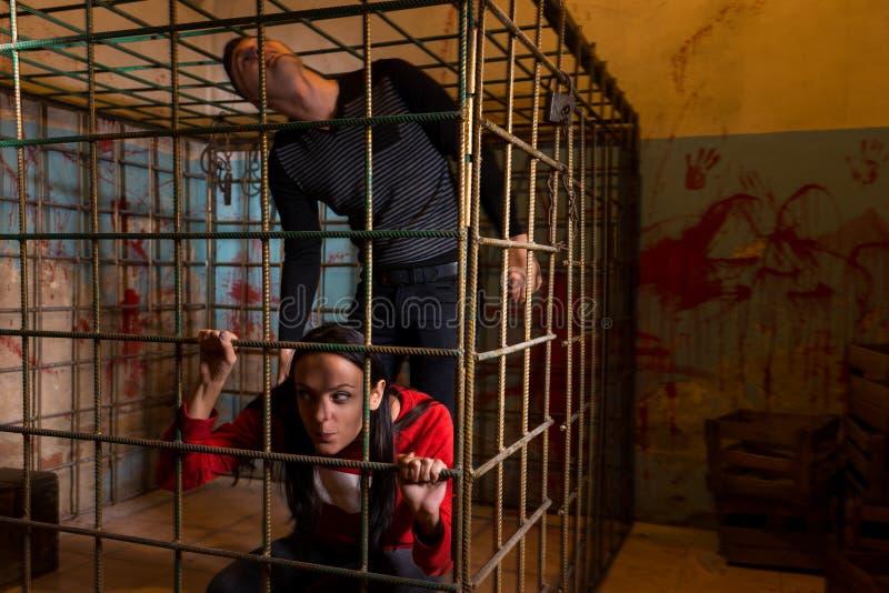 Coppie delle vittime spaventate di Halloween incarcerate in un lo della gabbia del metallo fotografie stock