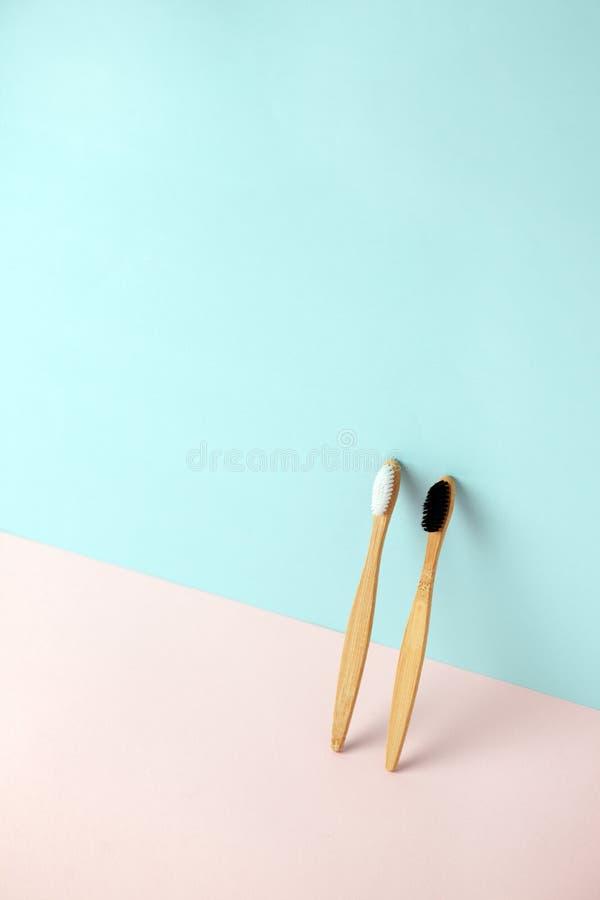 Coppie dello spazzolino da denti di bamb? sul fondo blu rosa dell'imitazione della rappresentazione 3d Spreco zero, sicuro il con fotografia stock libera da diritti