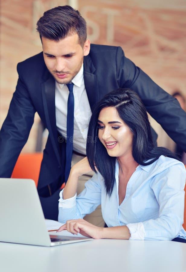 Coppie di affari in un ufficio che lavora al computer immagine stock libera da diritti
