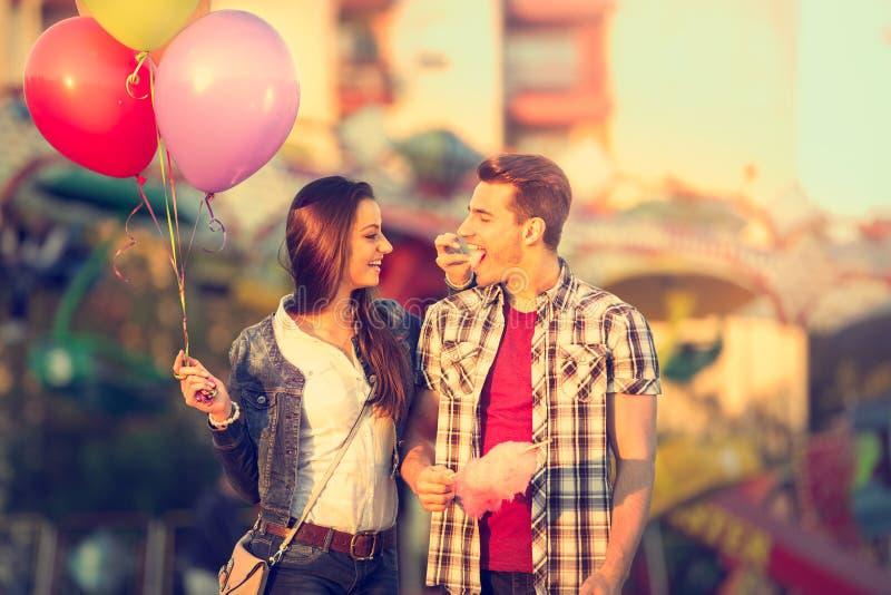 Coppie di amore in parco di divertimenti con lo zucchero filato immagini stock