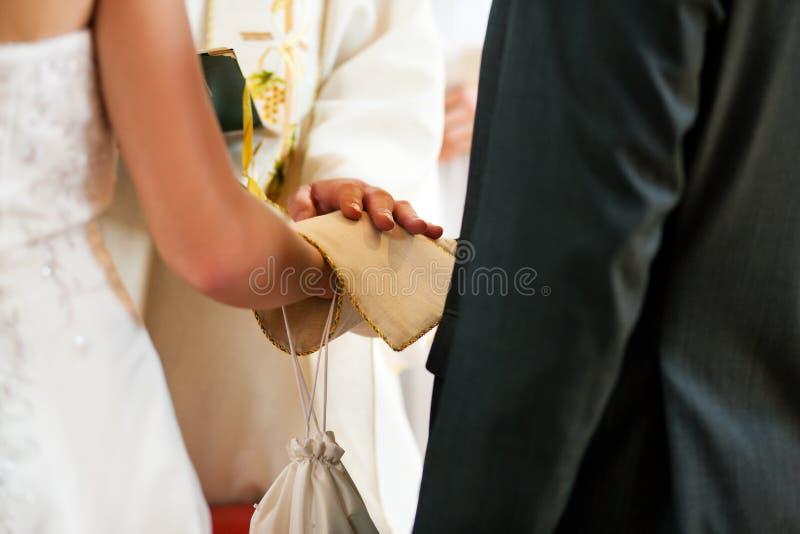 Coppie di cerimonia nuziale che ricevono benedizione dal sacerdote immagine stock