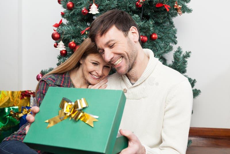 Coppie di divertimento che aprono un regalo di natale immagini stock libere da diritti