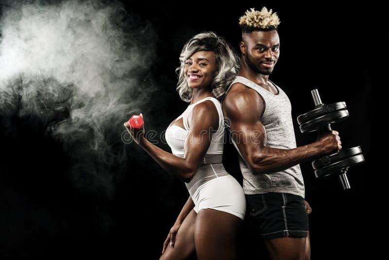 Coppie di forma fisica degli atleti che posano sul fondo nero, cura sana del corpo di stile di vita Concetto di sport con lo spaz immagine stock