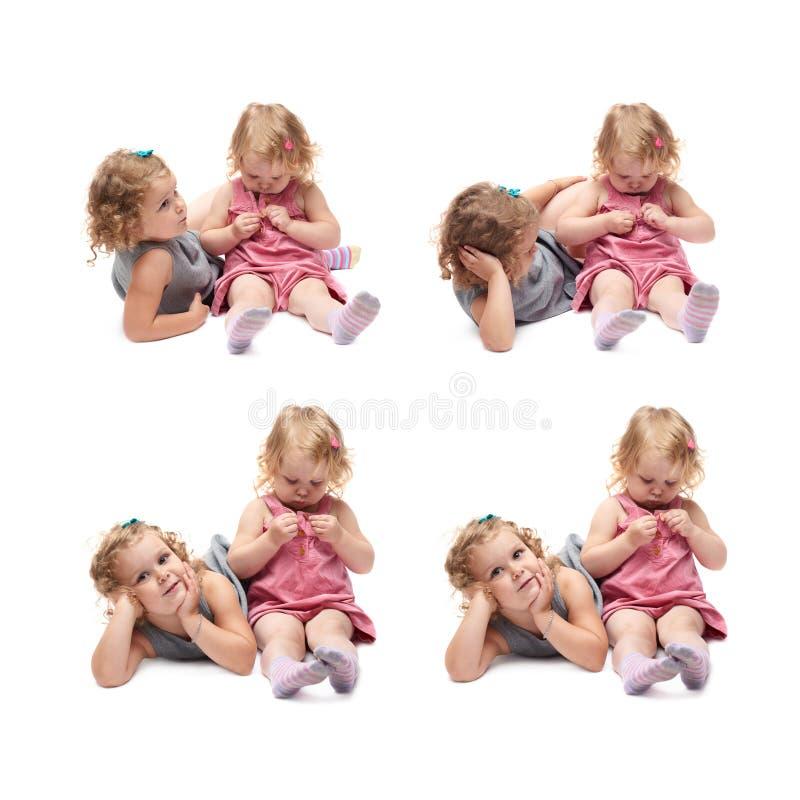 Coppie di giovane bambina che si siedono sopra il fondo bianco isolato fotografia stock