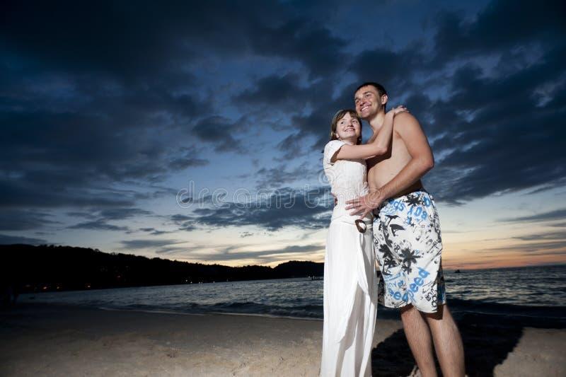 Coppie di giovani amanti sulla spiaggia fotografia stock libera da diritti