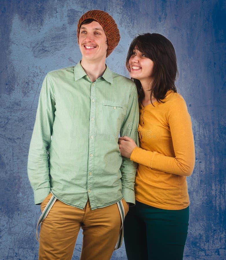 Coppie di giovani amici su un fondo blu immagine stock