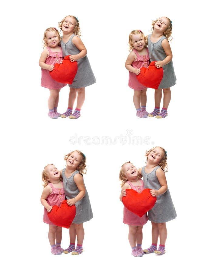 Coppie di giovani bambine che controllano fondo bianco isolato fotografie stock libere da diritti