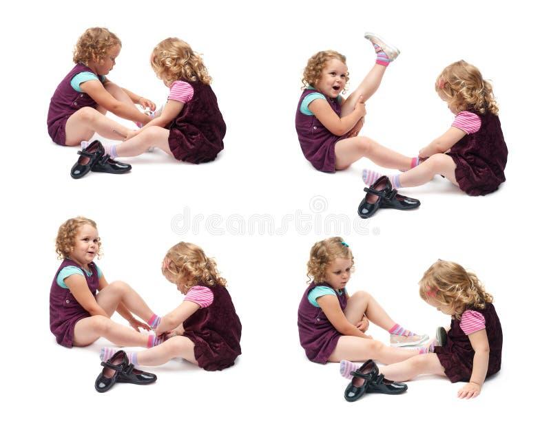 Coppie di giovani bambine che si siedono sopra il fondo bianco isolato fotografie stock