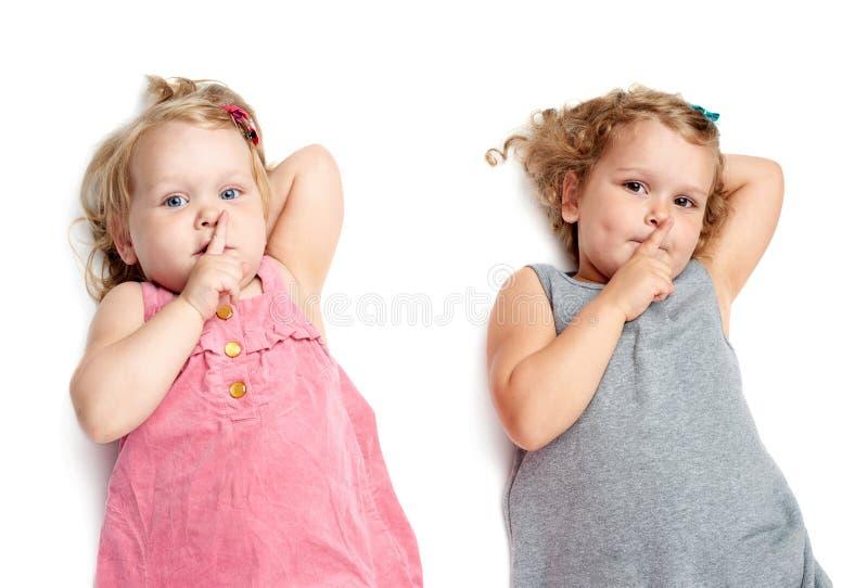 Coppie di giovani bambine che si trovano sopra il fondo bianco fotografie stock