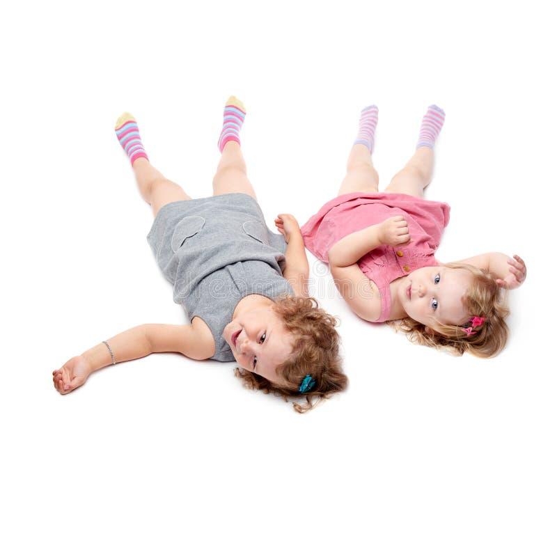 Coppie di giovani bambine che si trovano sopra il fondo bianco fotografie stock libere da diritti