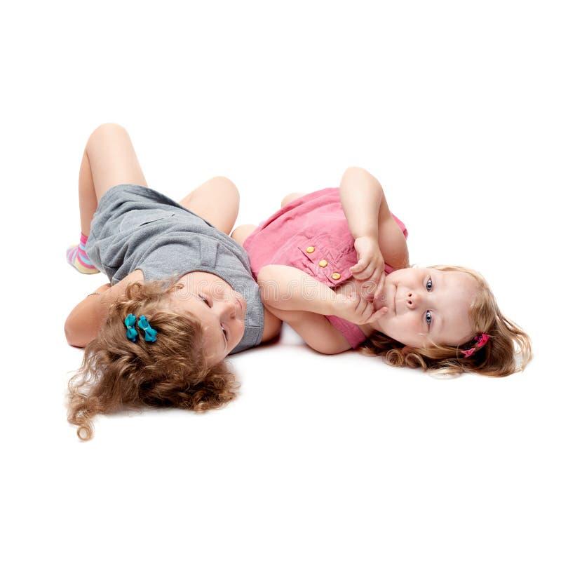 Coppie di giovani bambine che si trovano sopra il fondo bianco isolato fotografie stock libere da diritti
