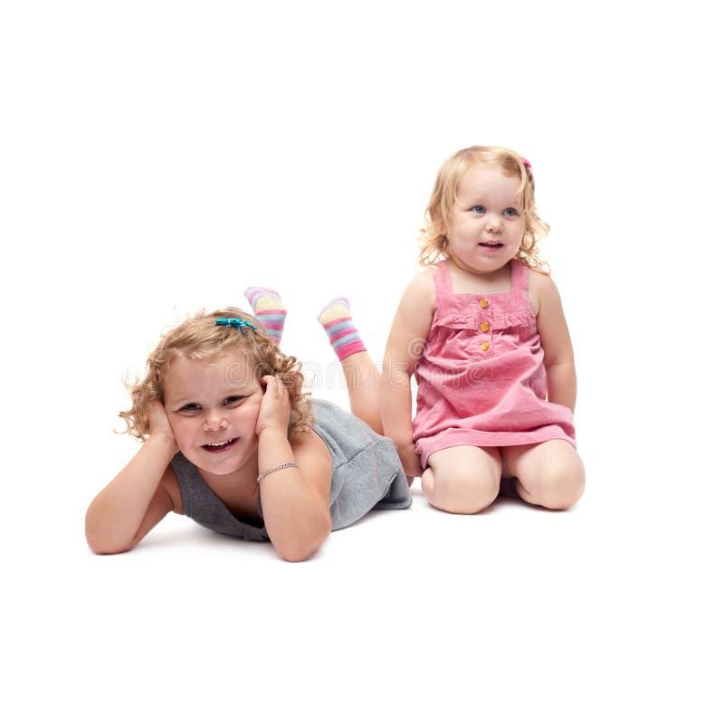 Coppie di giovani bambine che si trovano sopra il fondo bianco isolato immagine stock libera da diritti