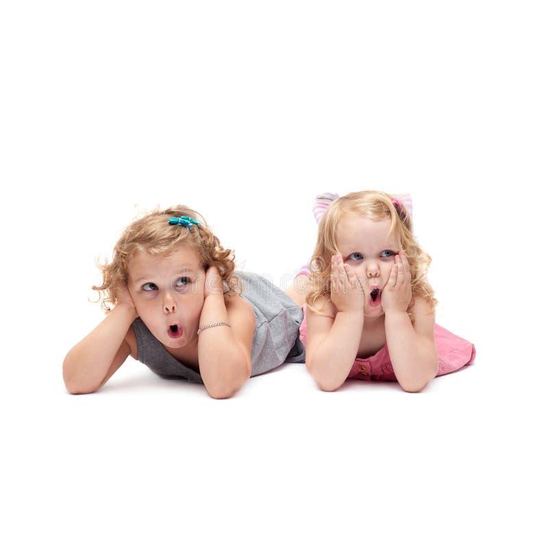 Coppie di giovani bambine che si trovano sopra il fondo bianco isolato immagini stock