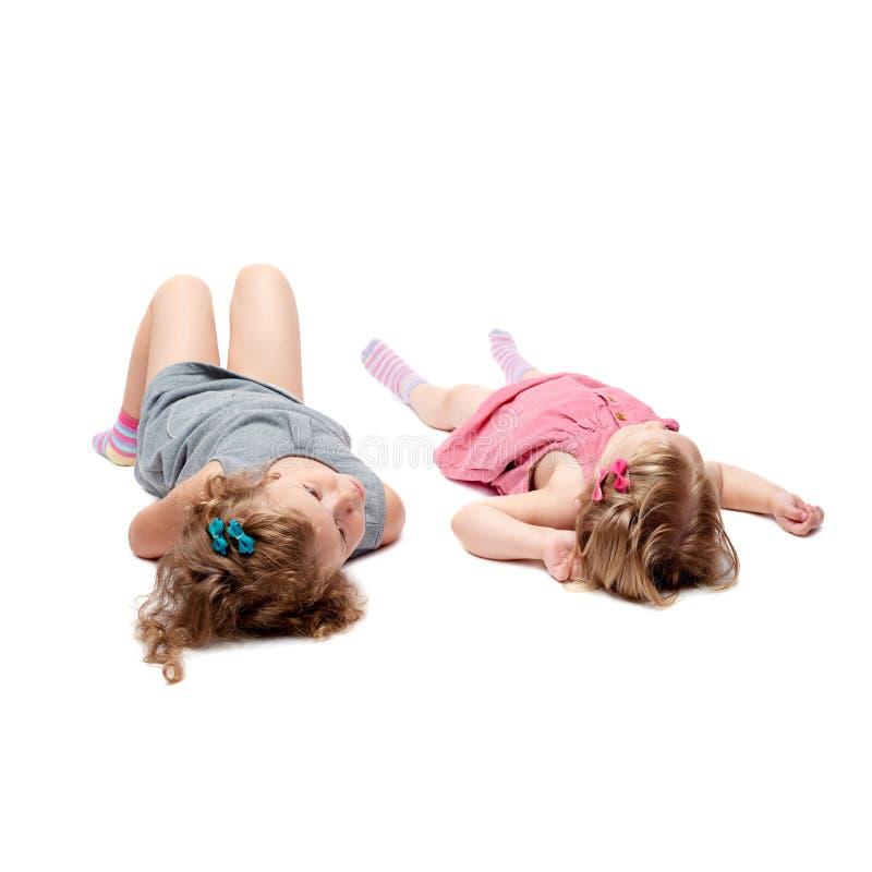 Coppie di giovani bambine che si trovano sopra il fondo bianco isolato fotografie stock