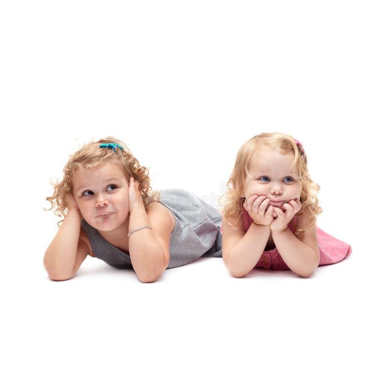 Coppie di giovani bambine che si trovano sopra il fondo bianco isolato fotografia stock