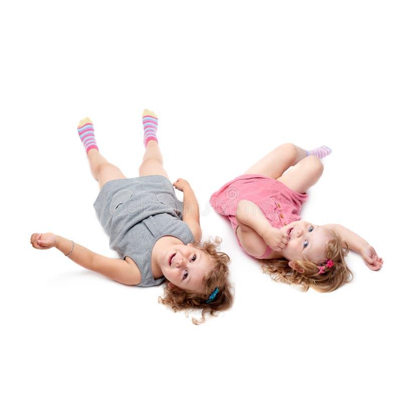 Coppie di giovani bambine che si trovano sopra il fondo bianco isolato fotografia stock libera da diritti