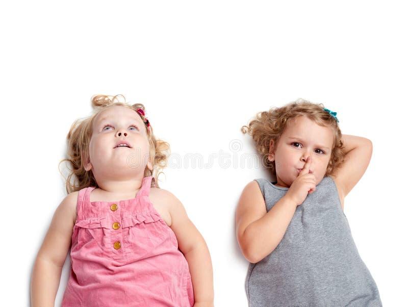 Coppie di giovani bambine che si trovano sopra il fondo bianco isolato immagini stock libere da diritti