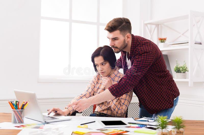 Coppie di giovani progettisti che lavorano all'ufficio moderno fotografie stock