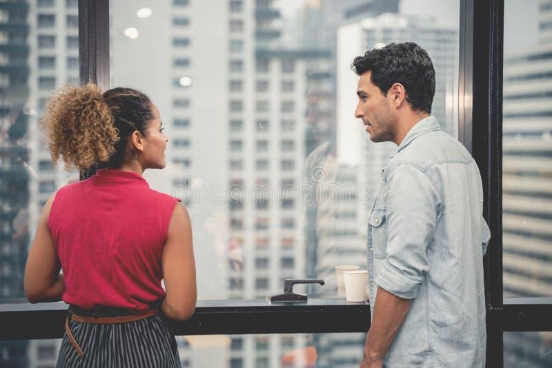 Coppie di giovani progettisti che lavorano all'ufficio moderno, due colleghe che discutono progetto sopra un computer portatile,  fotografia stock