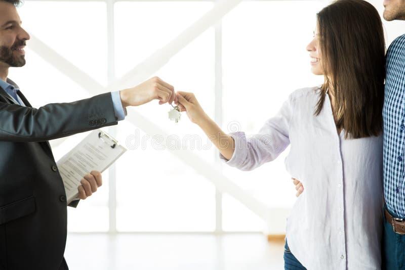 Coppie di Handing Keys To dell'agente immobiliare in nuovo appartamento immagini stock