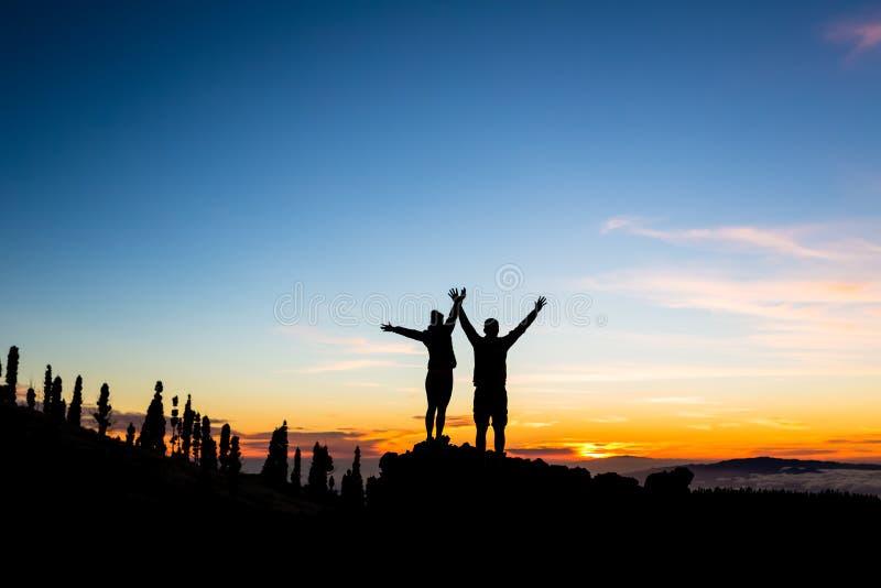 Coppie di lavoro di squadra che scalano e che raggiungono il picco di montagna immagini stock
