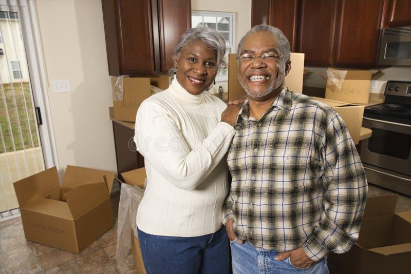 Coppie di mezza età che si levano in piedi nella cucina con le caselle. fotografie stock libere da diritti