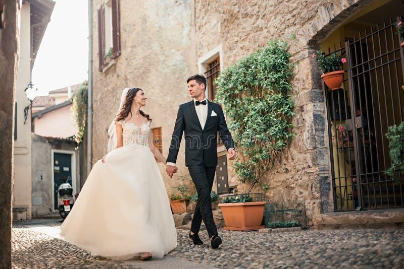 Coppie di nozze che camminano giù una via immagini stock libere da diritti