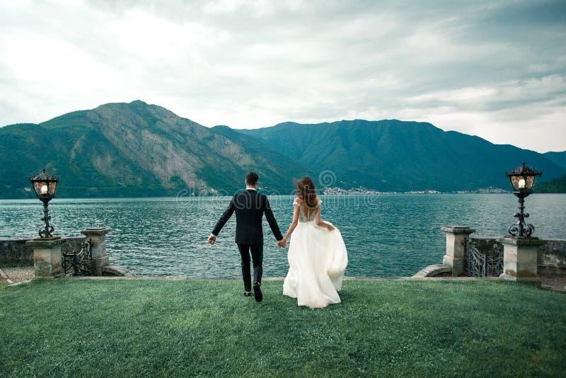 Coppie di nozze che corrono avanti contro lo sfondo del lago e delle montagne immagini stock libere da diritti