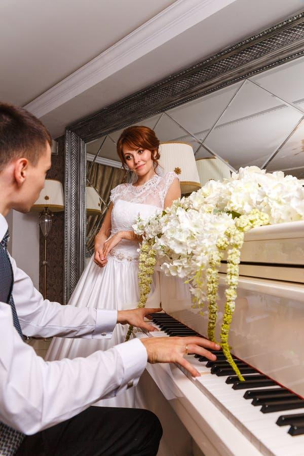 Coppie di nozze che giocano su un piano immagini stock