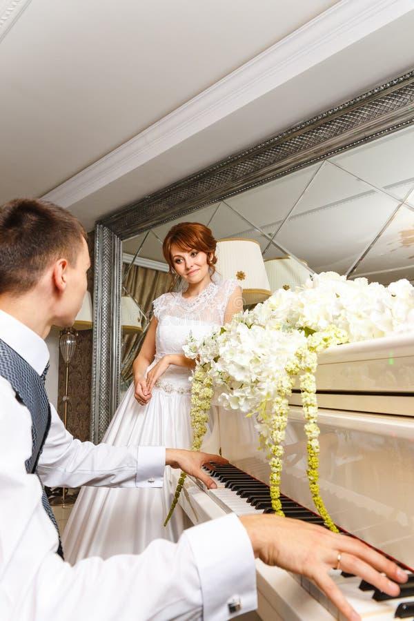 Coppie di nozze che giocano su un piano fotografia stock libera da diritti