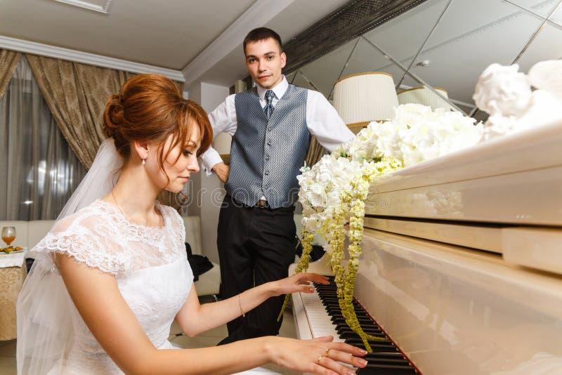 Coppie di nozze che giocano su un piano immagine stock