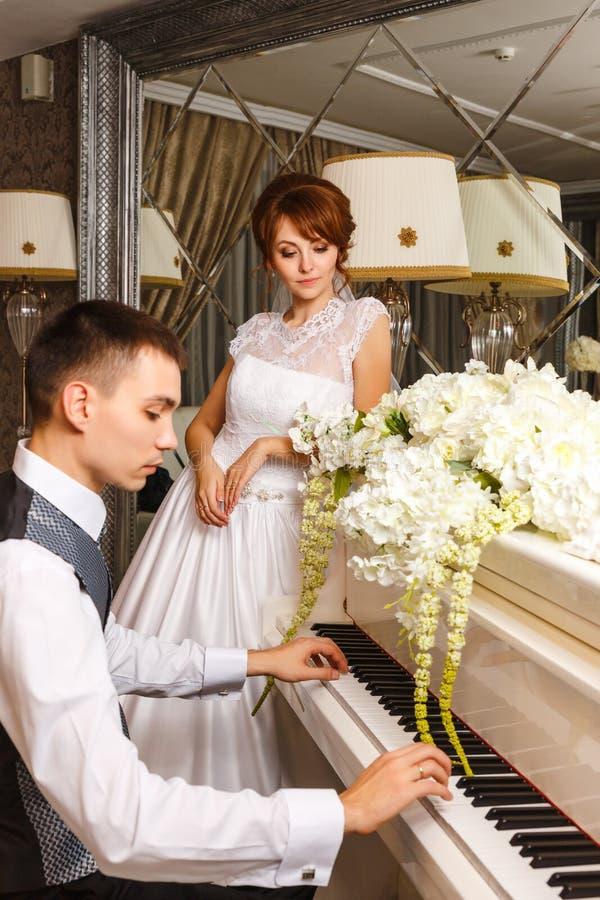 Coppie di nozze che giocano su un piano fotografia stock