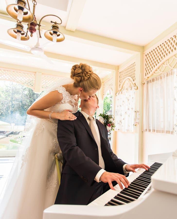 Coppie di nozze che giocano su un piano nella stanza fotografie stock