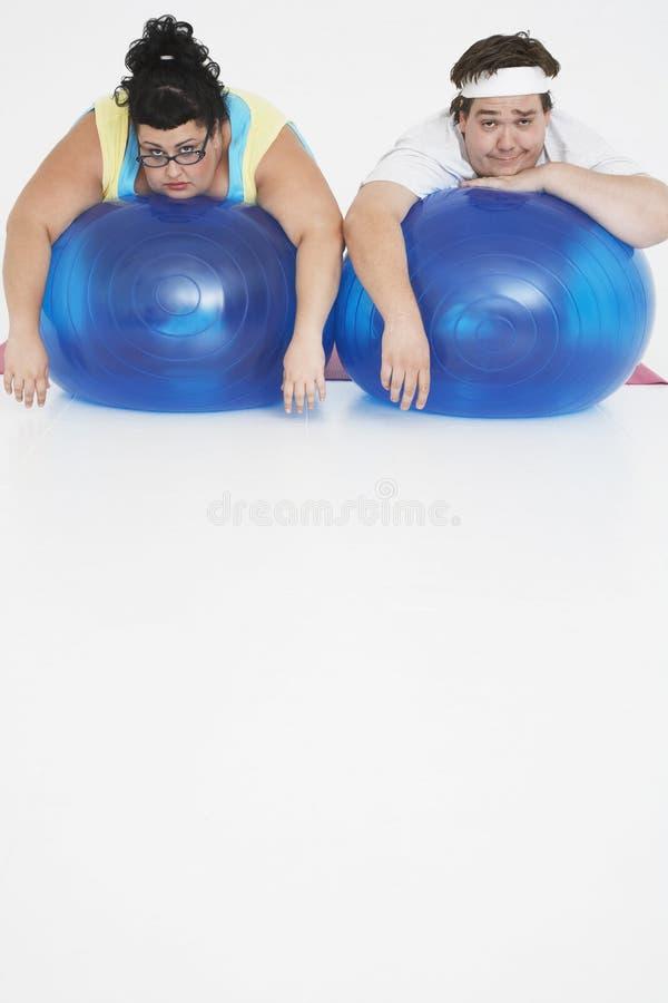 Coppie di peso eccessivo che riposano sulle palle di esercizio immagine stock libera da diritti