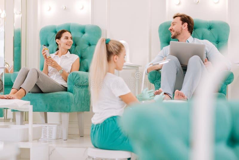 Coppie di riusciti uomini d'affari che vengono al salone per il massaggio dei piedi immagini stock