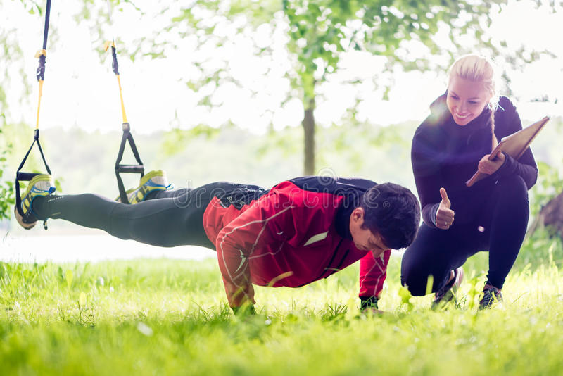 Coppie di sport all'aperto con l'istruttore dell'imbracatura fotografie stock