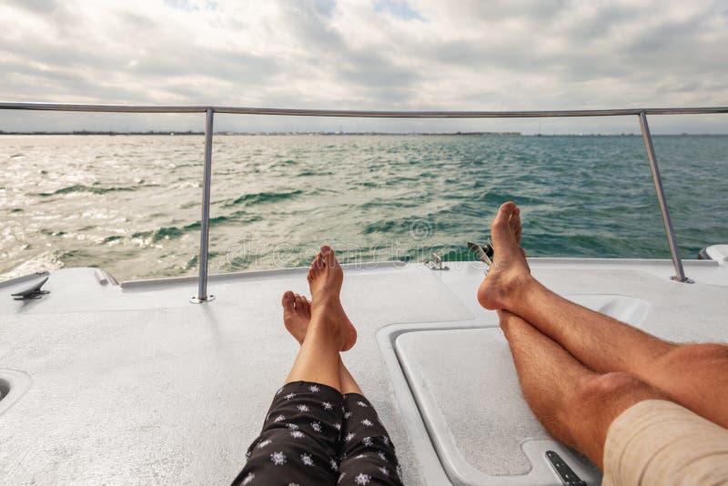 Coppie di stile di vita del crogiolo di yacht che si rilassano sulla nave da crociera nella festa delle Hawai Due piedi dei turis immagini stock libere da diritti