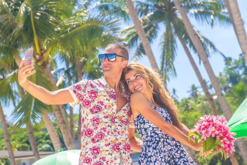 Coppie di vacanza sulla spiaggia che prende le immagini con il telefono della macchina fotografica roma fotografia stock