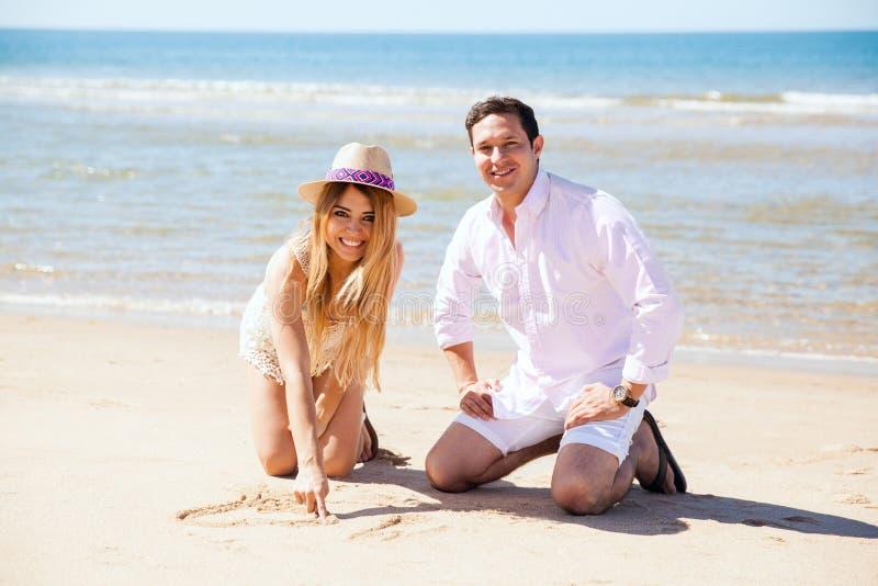 Coppie divertendosi con la sabbia fotografie stock