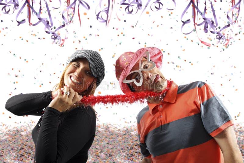 Coppie divertenti che godono di un partito di carnevale fotografia stock