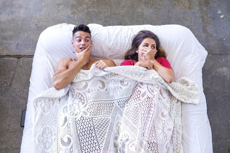 Coppie divertenti che si trovano a letto con la mano sul fronte immagini stock libere da diritti