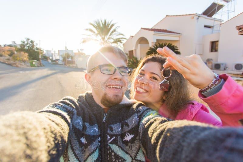 Coppie divertenti con le chiavi che stanno nuova casa esterna Concetto del bene immobile, del proprietario e della gente fotografia stock