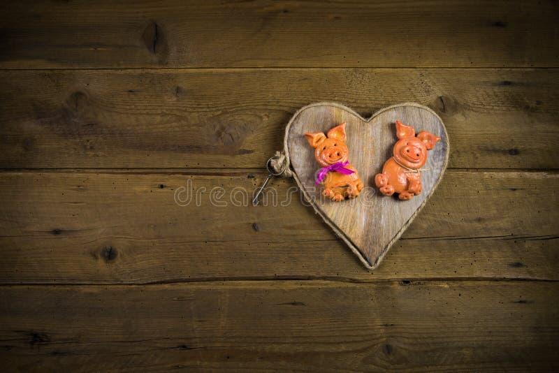 Coppie divertenti del maiale della pasta del sale su un cuore con fondo di legno fotografie stock